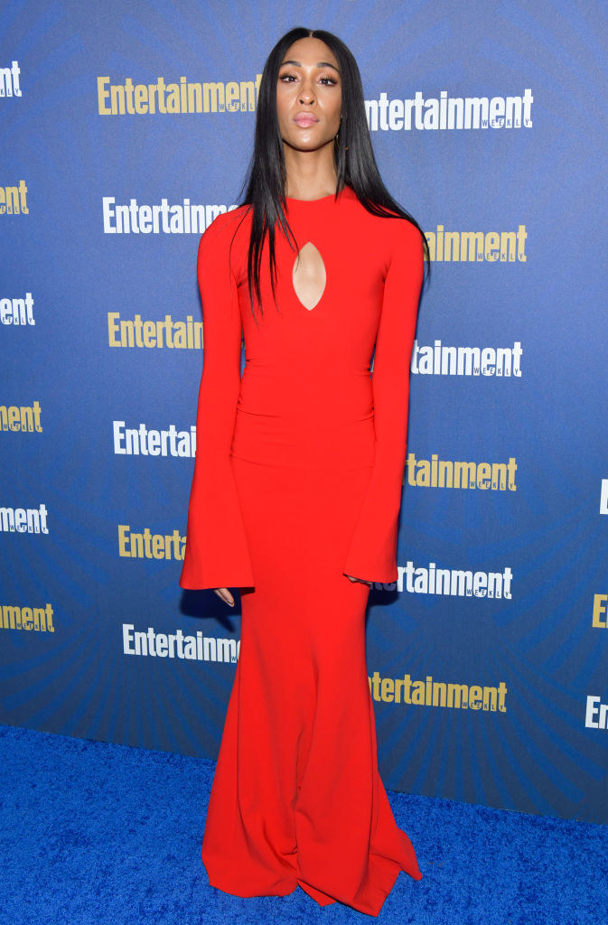 Mj Rodriguez wears a floor length red baggy gown.