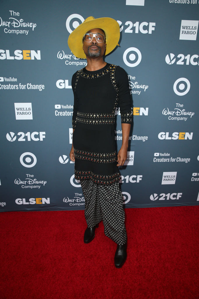 Billy Porter in a long, tight, decorated shirt and flowing patterned pants
