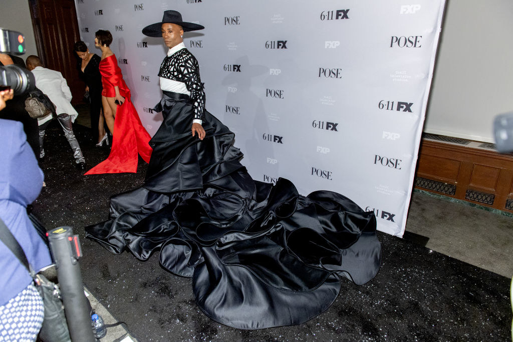 Billy Porter in a long black dress with a ruffled train