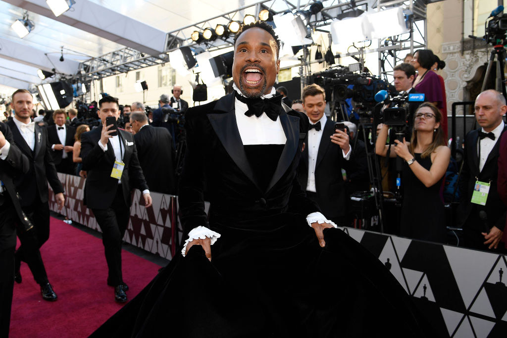 Billy Porter walking down the red carpet in a suit with a large black skirt