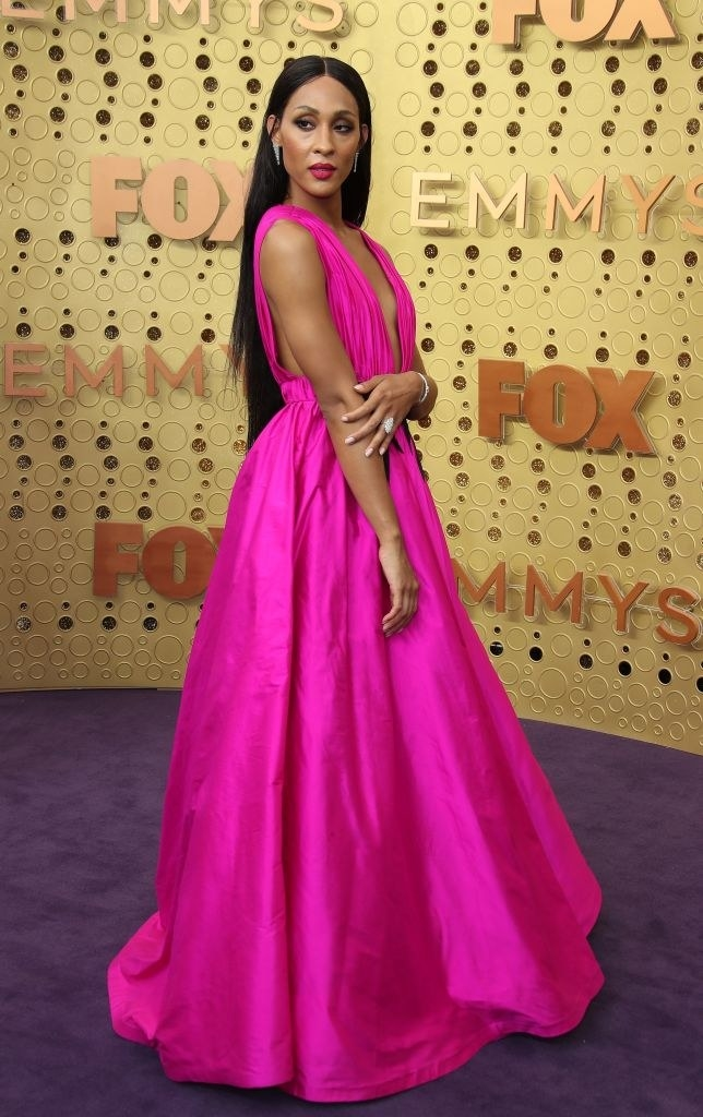 Mj Rodriguez wears a floor length bright pink gown.