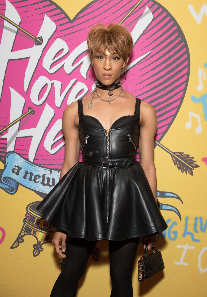 Mj Rodriguez wears a leather mini dress on top of tights and a metal choker.