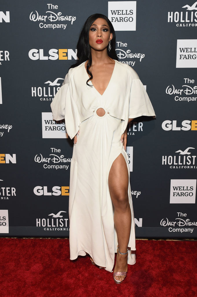 MJ Rodriguez wears an ankle length white gown with a slit up the leg.