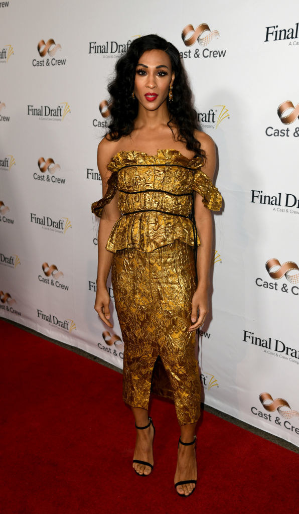 Mj Rodriguez wears a gold foil material ankle length dress.