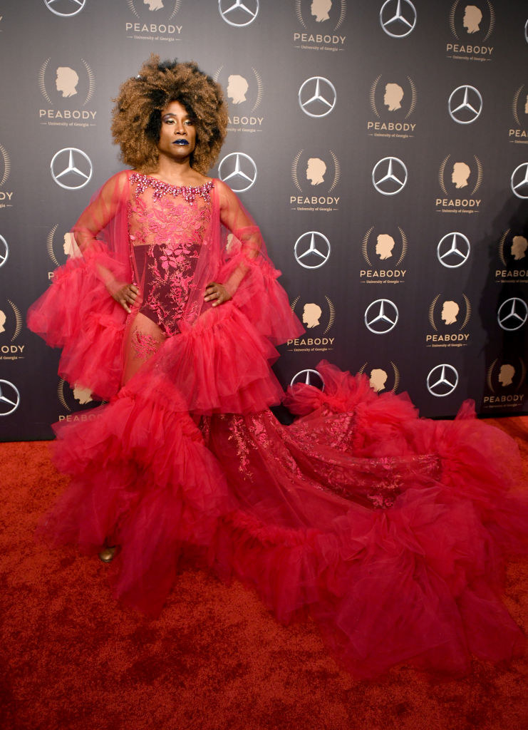 Billy Porter in an ornate red gown with a tulle train