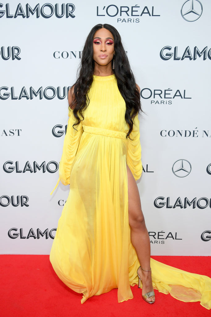 MJ Rodriguez wears a yellow floor length gown with a slit on one side.