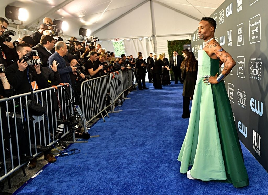Billy Porter posing in a flowing green gown