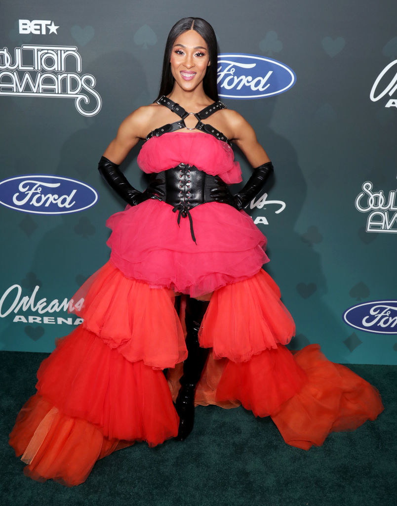 Mj Rodriguez wears a pink and red ruffle gown held together with a leather bodice.