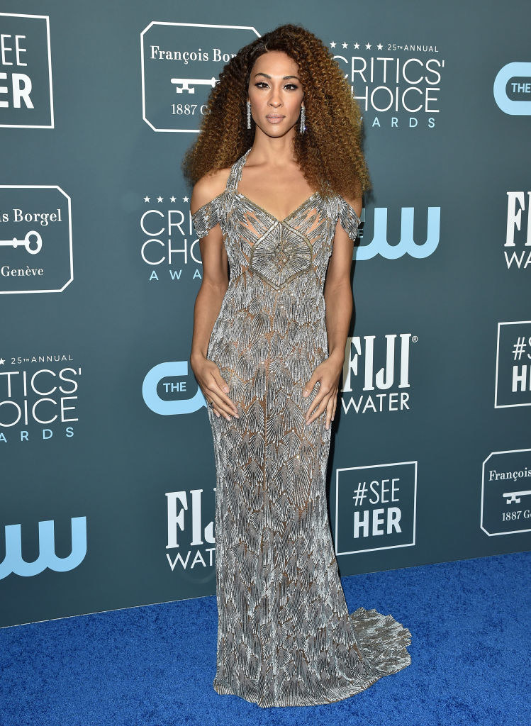 Mj Rodriguez wears a big curly wig and an off the shoulder floor length gown.