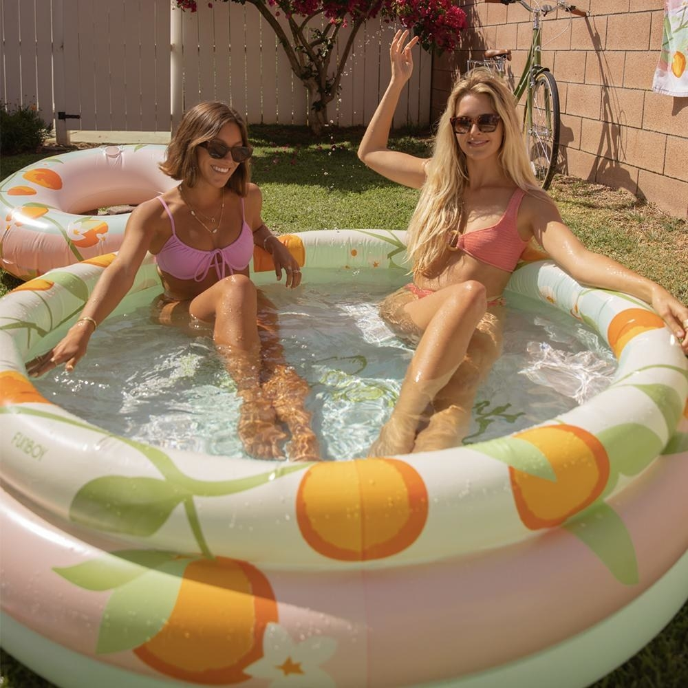 two adults sitting in a large kiddie pool with oranges printed on it