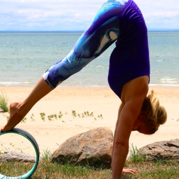 Person standing on their hands and bent in an acute angle, with their toes pointing down while balancing on the wheel