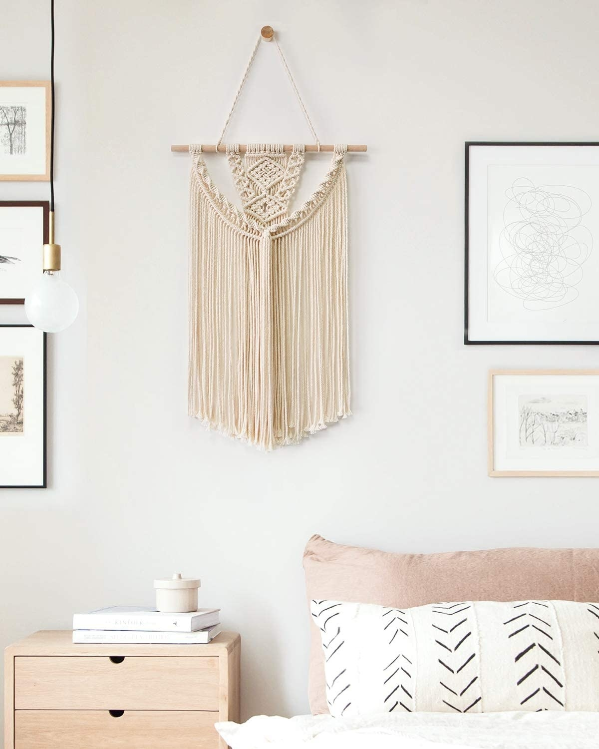 a hanging macrame wall piece in a bedroom