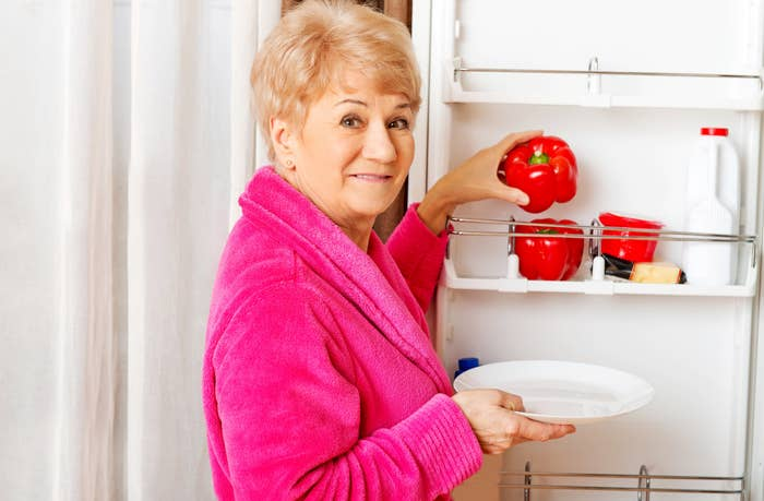 An old woman getting stuff from her fridge