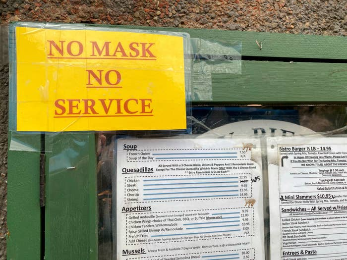 """A sign posted outside a restaurant in Queens, New York, reads """"no mask, no service"""""""