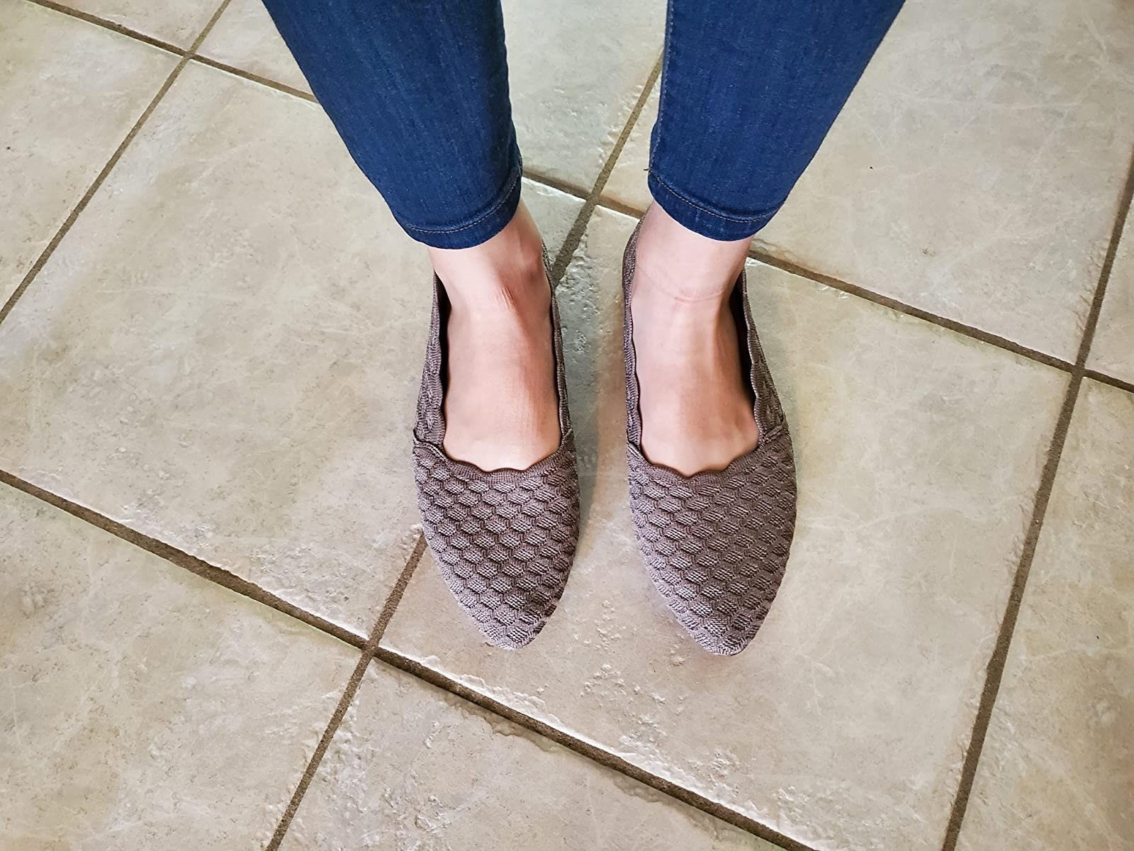 reviewer in the almond-toe, scallop-pattern flats in a dark taupe
