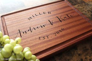 a wood cutting board that says andrew and kate est 206