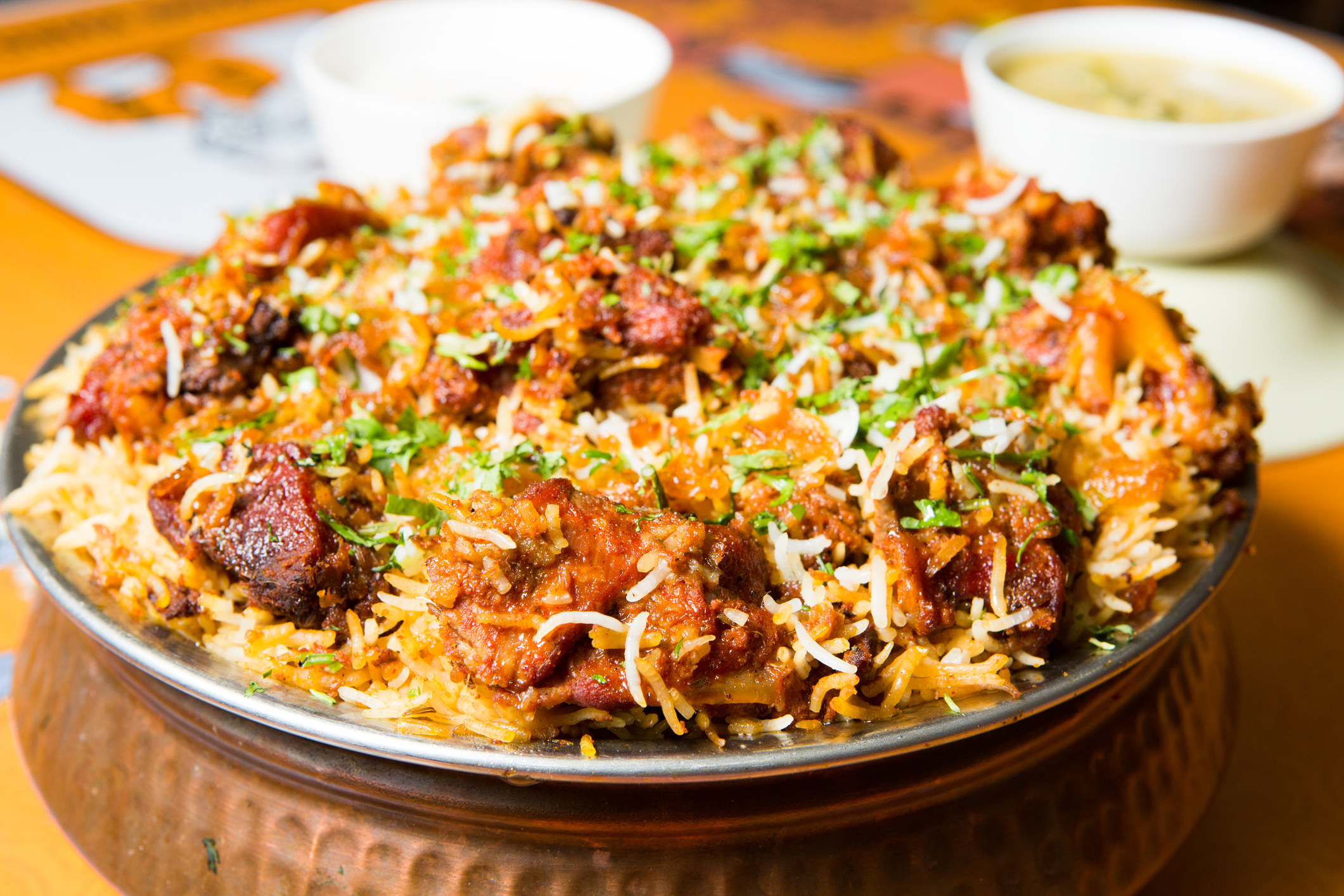 A bowl of Indian biryani with cubed meat.