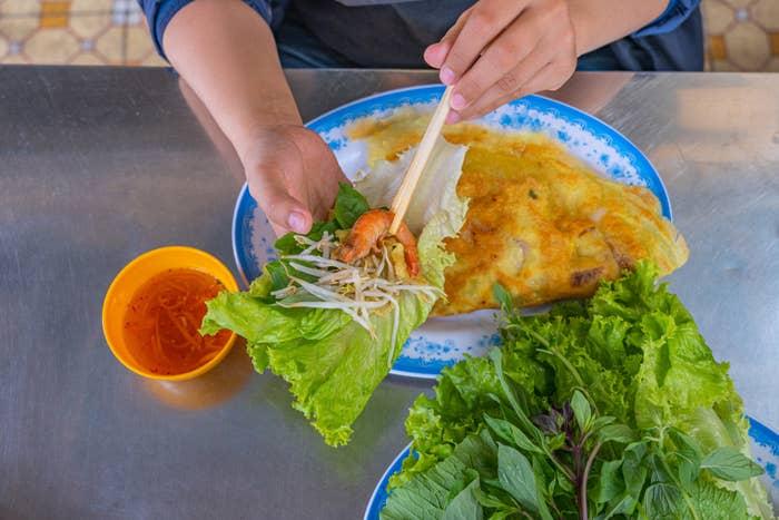 A woman putting Vietnamese crepe into a lettuce wrap.