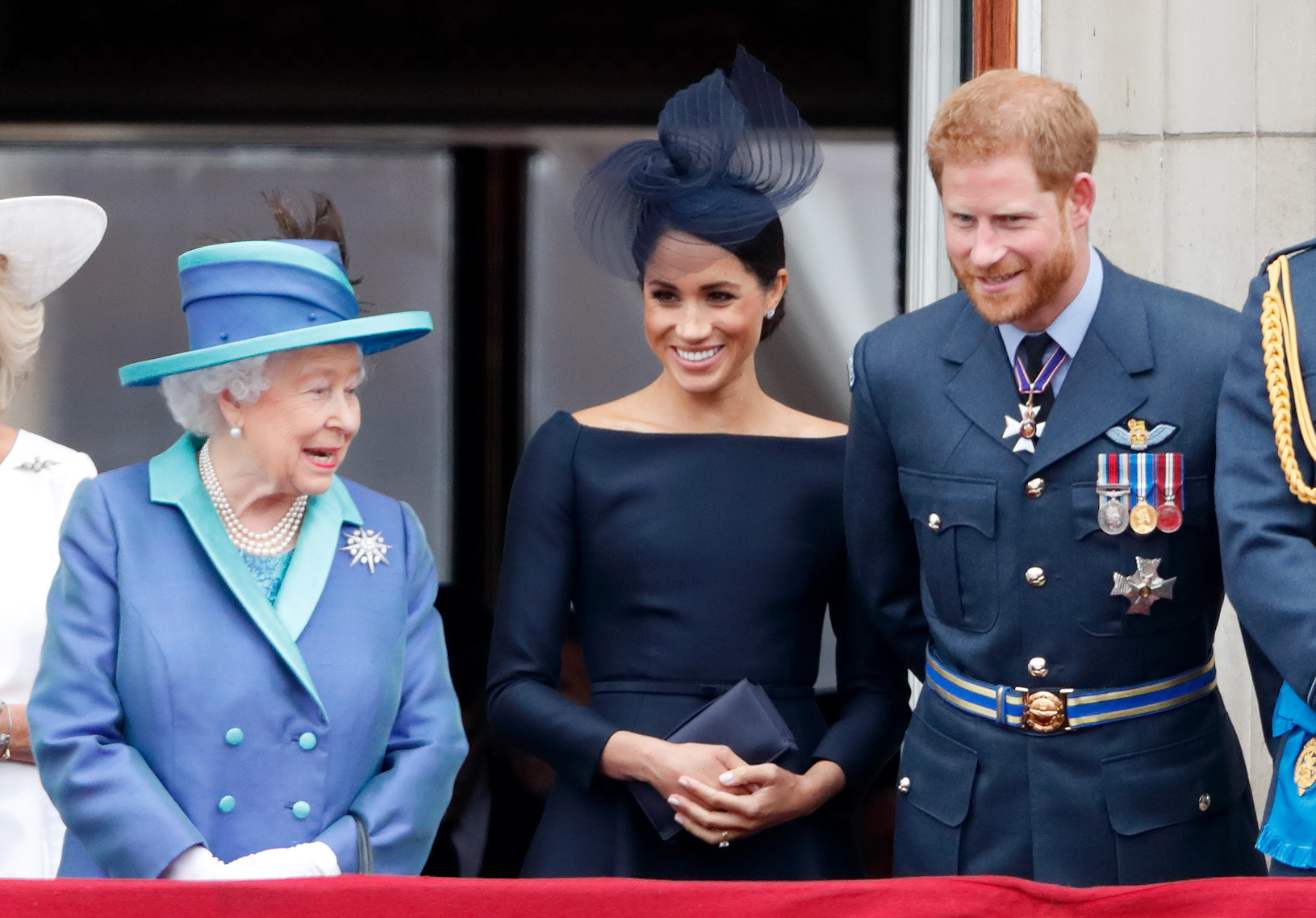 Meghan and Harry stand next to the Queen