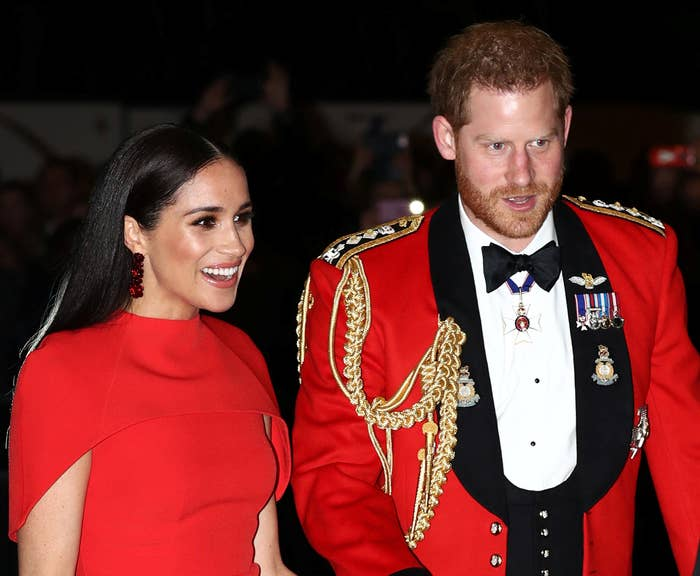 Meghan wears a red dress while Harry wears a red jacket with metals