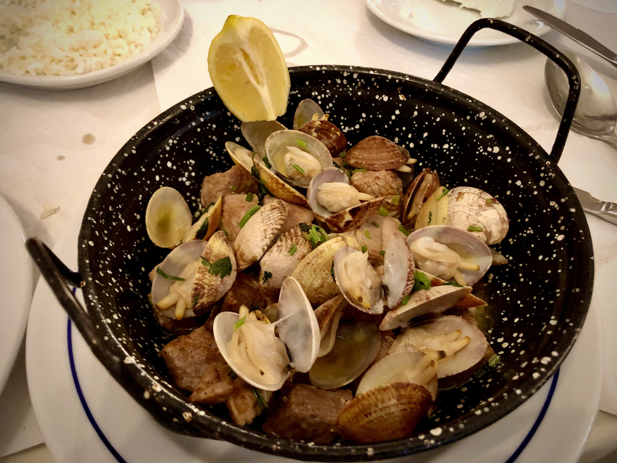 Portuguese pork and clams in a wok.