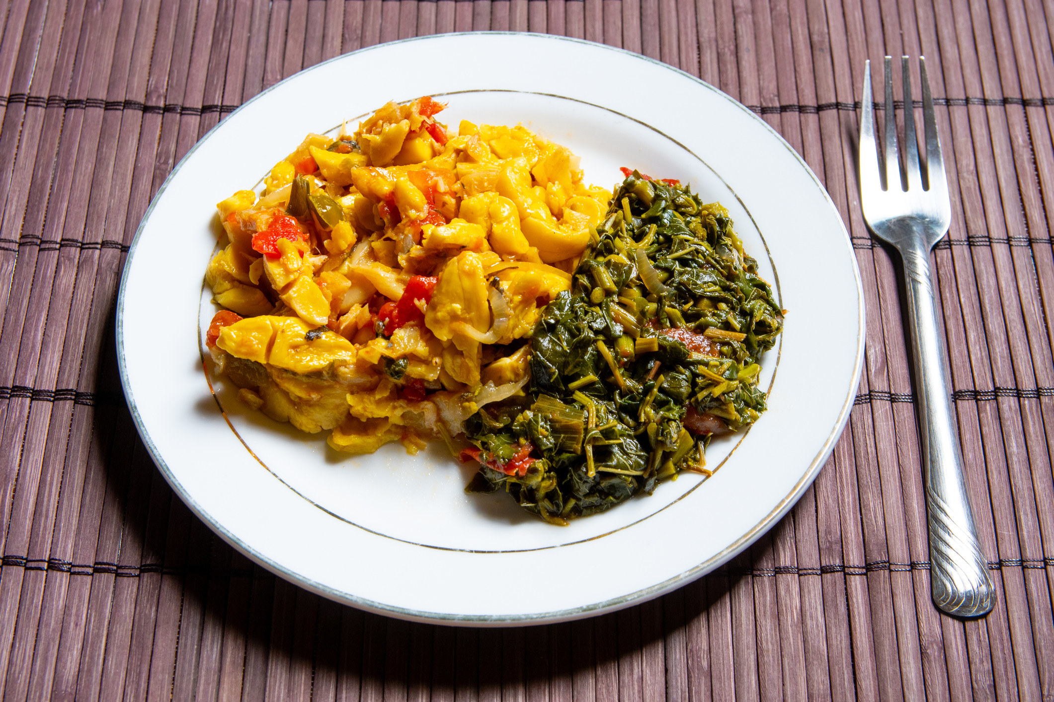 A plate of Jamaican ackee and saltfish with steamed callaloo.