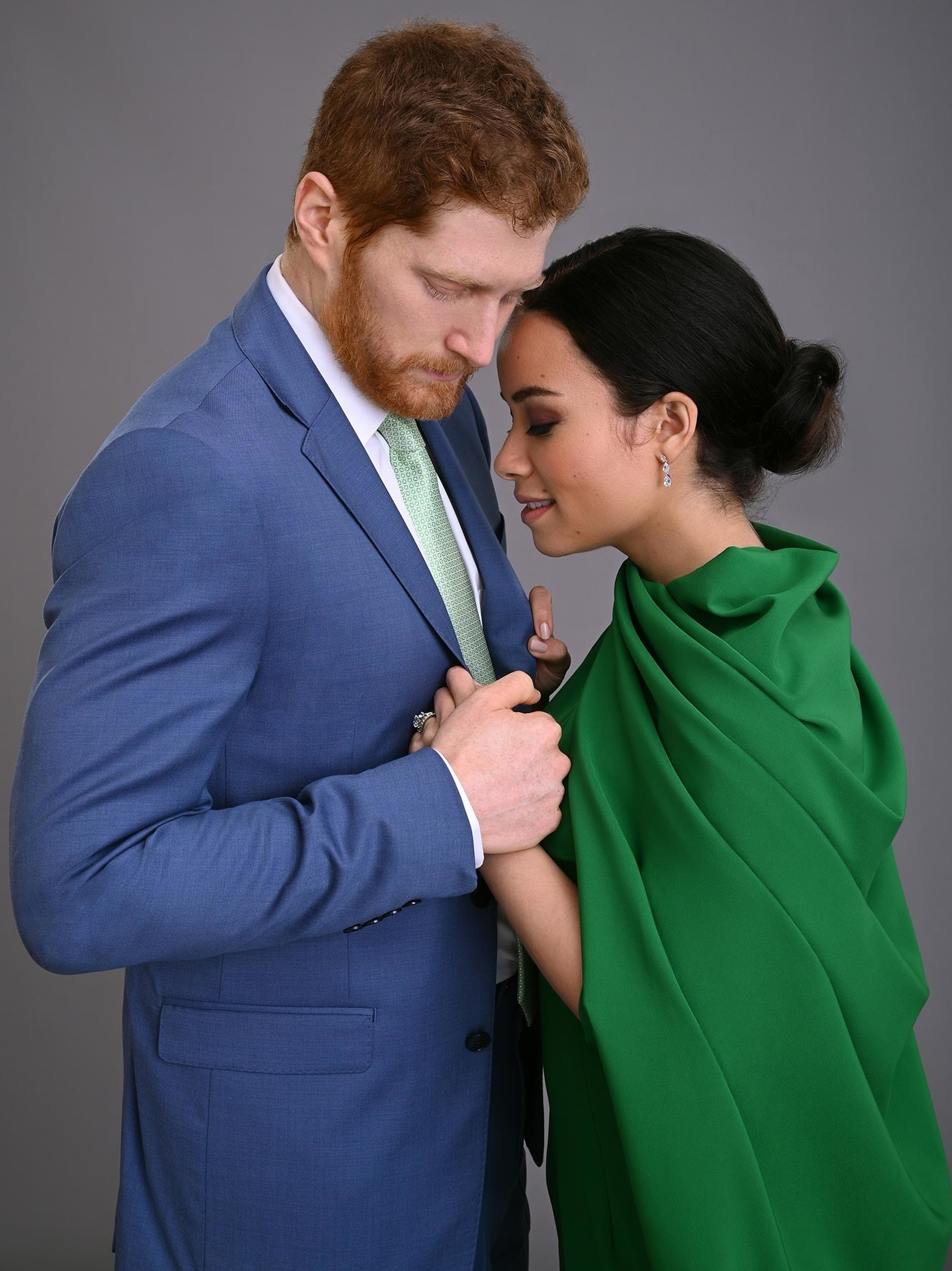 The actors playing Meghan and Harry face each other and hold hands