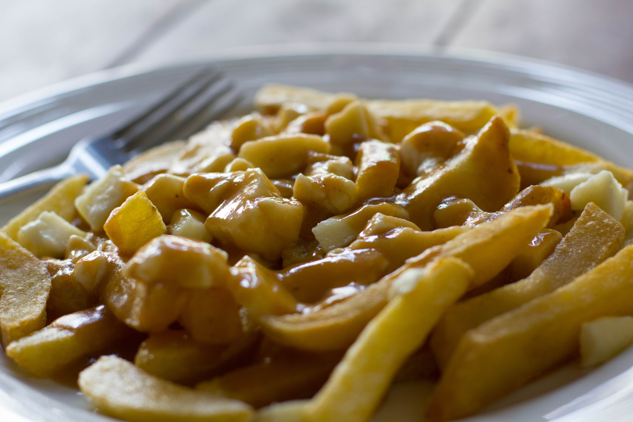 A plate of poutine with gravy and cheese curds.