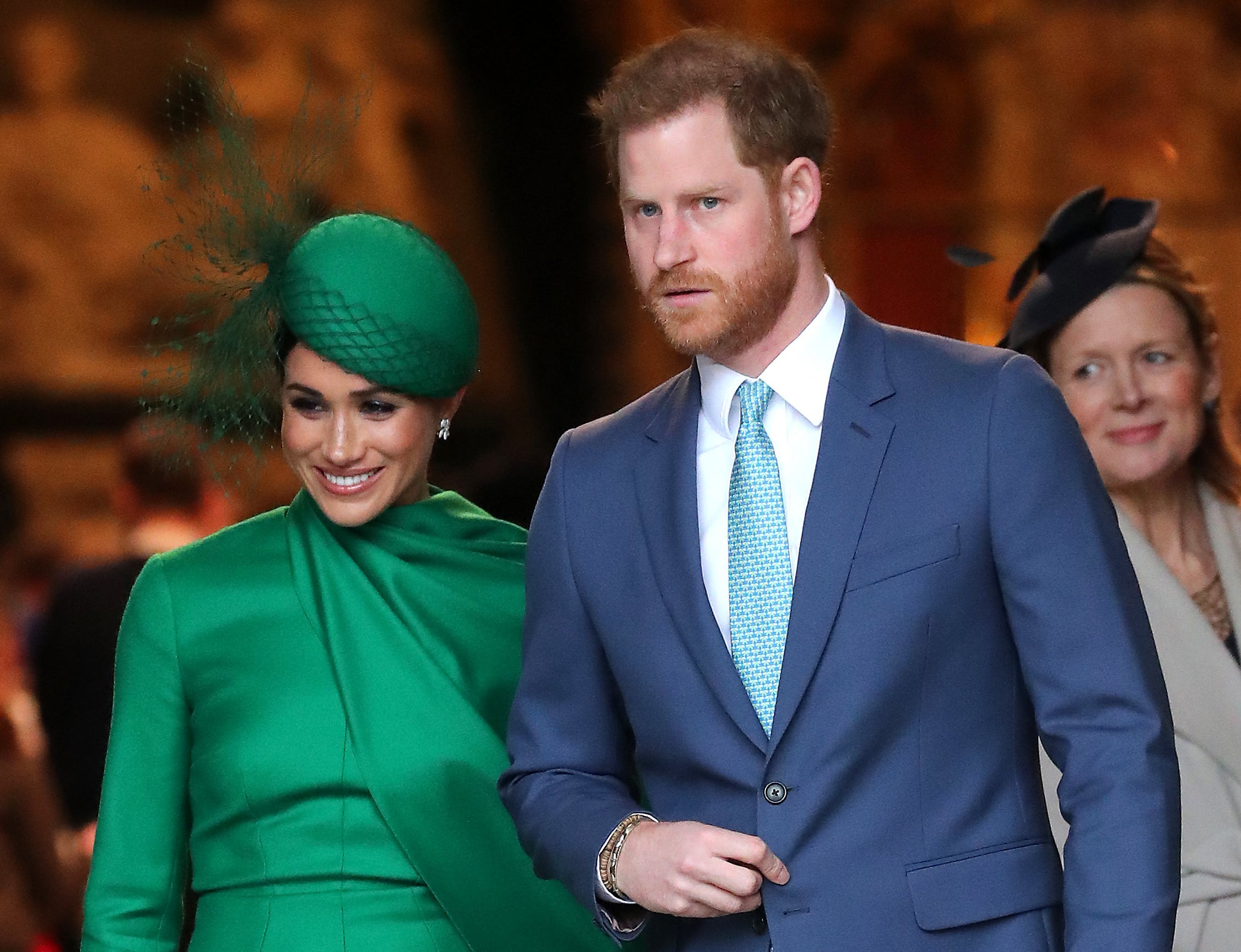Meghan wears an green dress and hat while walking with Harry