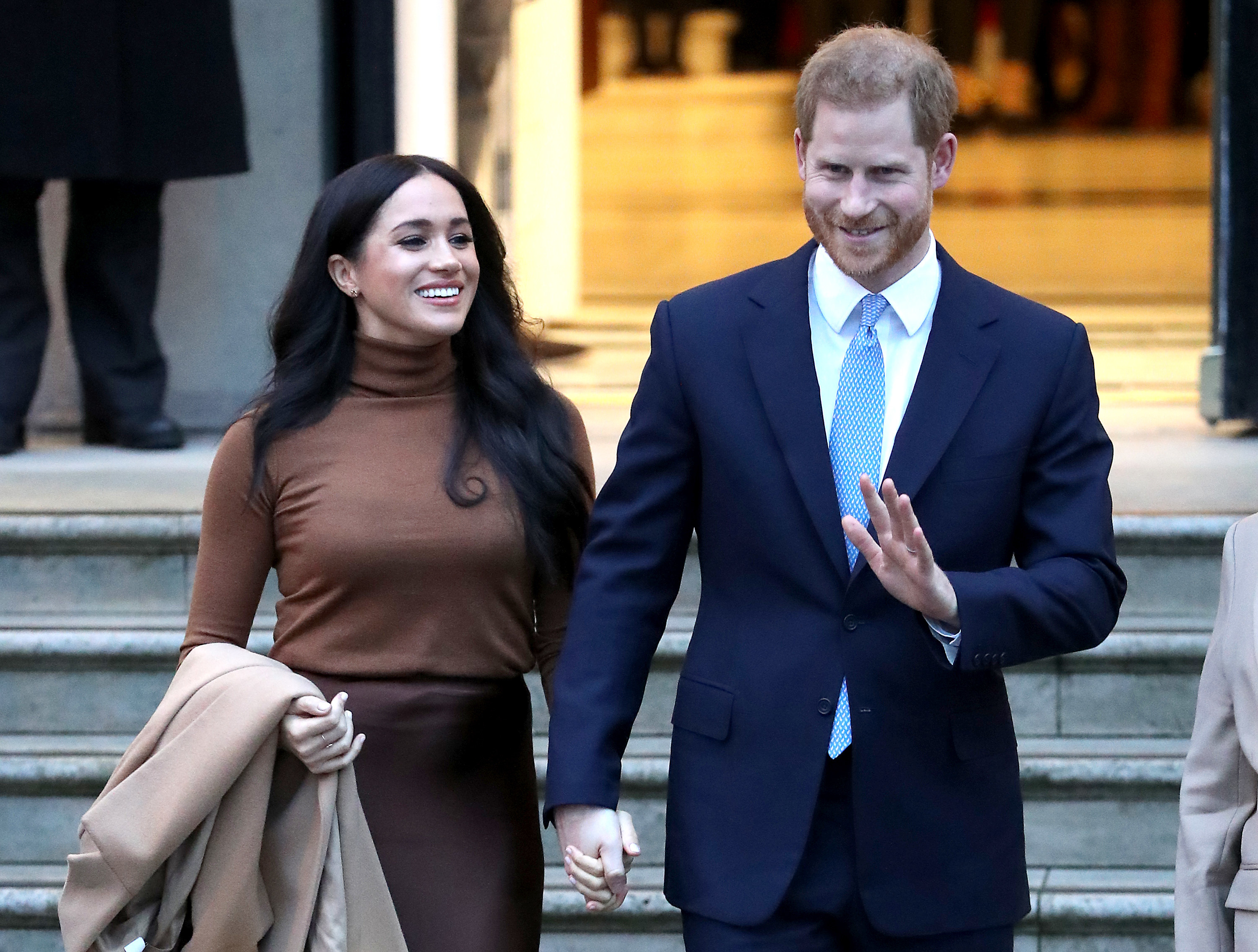 Prince Harry waves while leaving a building with Meghan