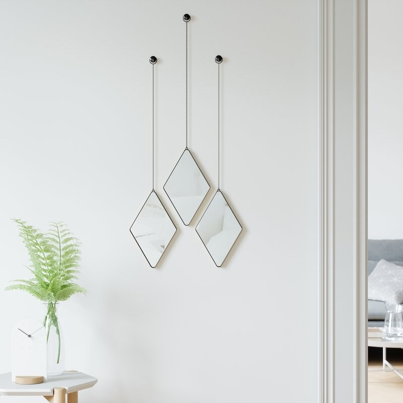 Mirrors hanging from thin black hardware