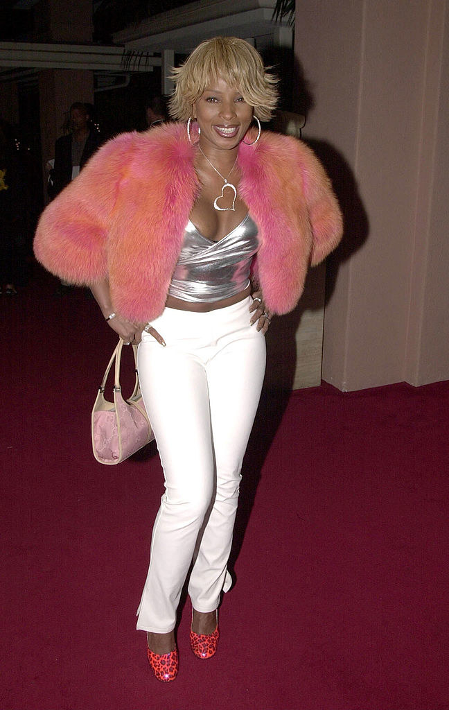 Mary in a bright, fluffy, cropped jacket with simple pants and a necklace with a diamante heart on it