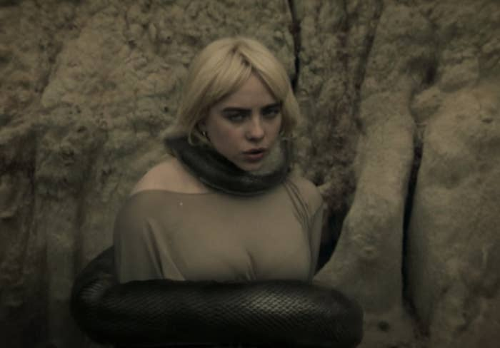 Billie singing in the music video with a large snake wrapping itself around her body