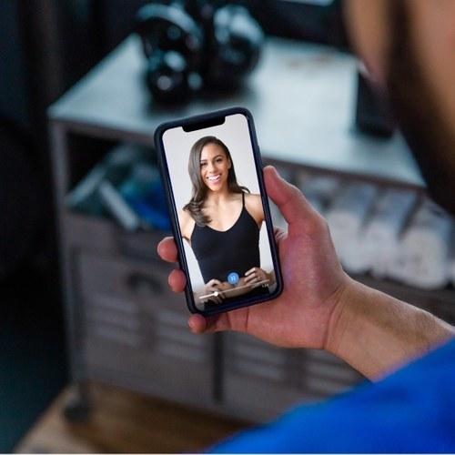 Human holding phone featuring the trainiac app.