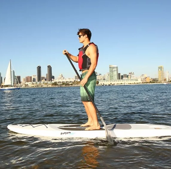 A man stands on a white paddleboard