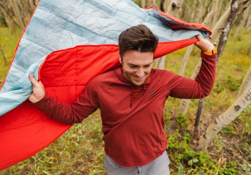 a man stands with a red blanket
