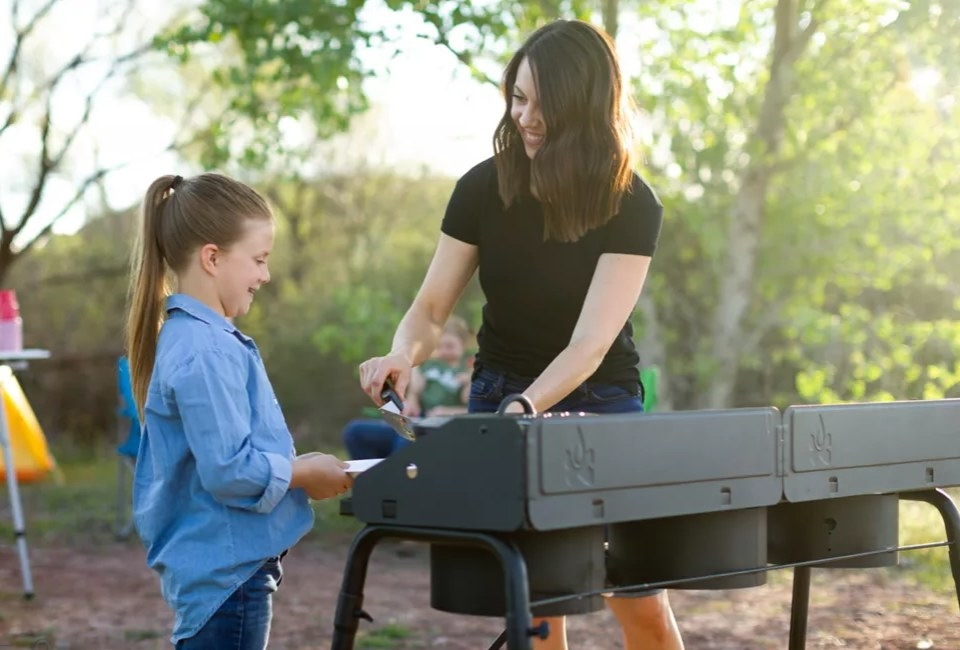 A woman and child stand by a grill