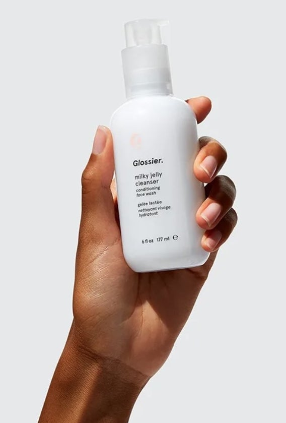 A model holding the cleanser