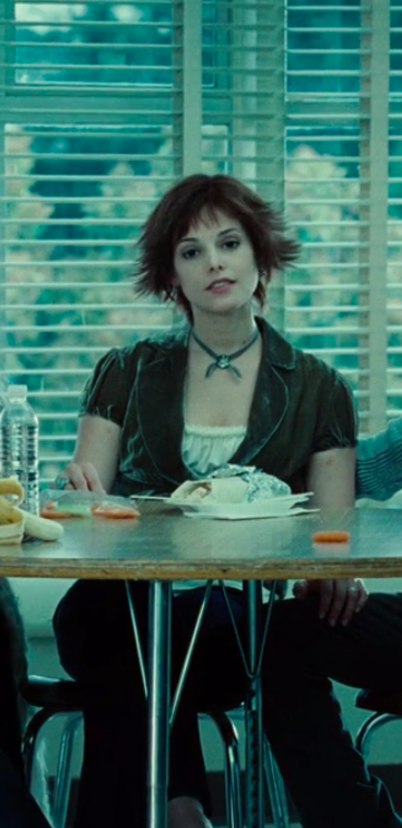Alice wearing pants, a flowy shirt, a vest, and a necklace