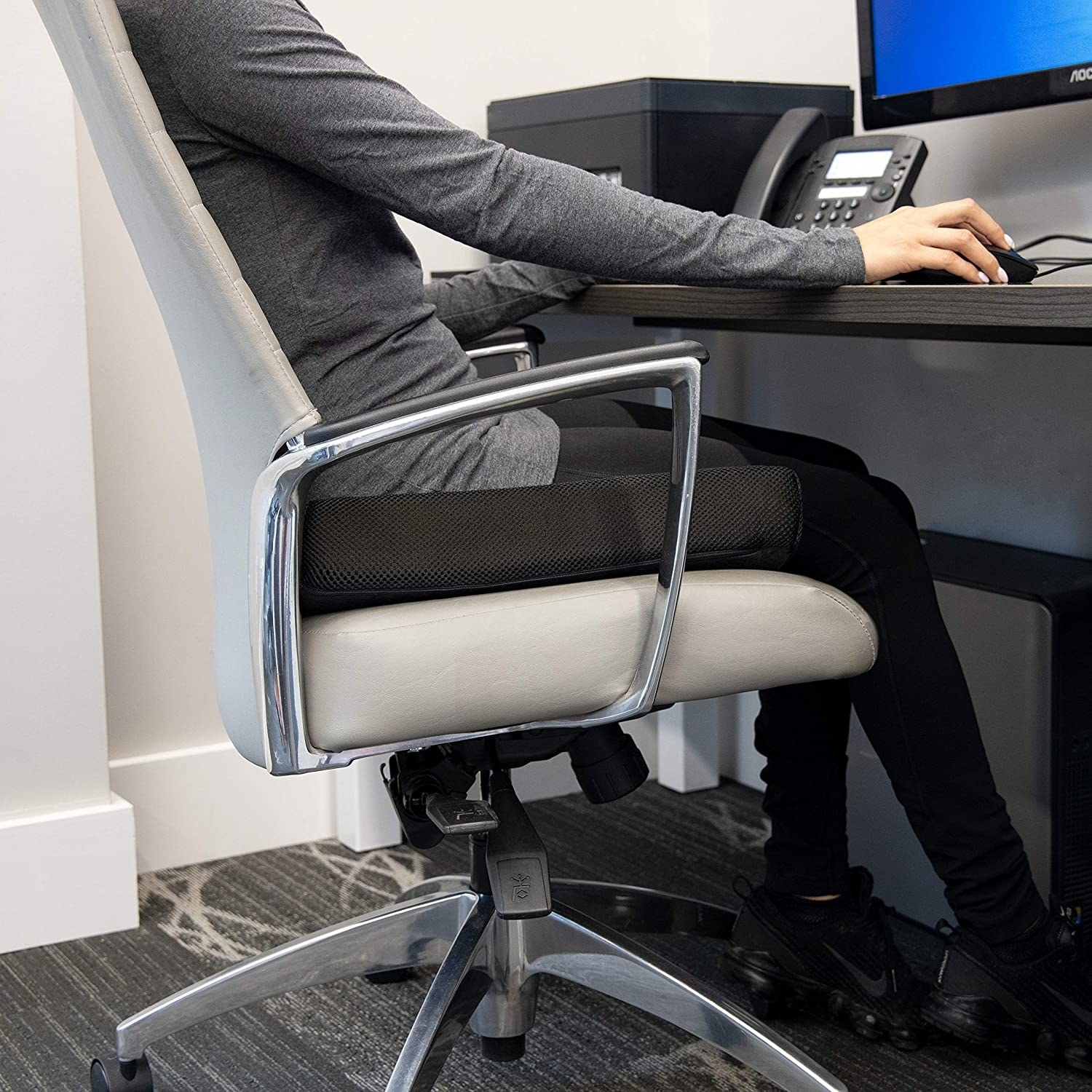 A person sitting on a chair with the cushion under their butt