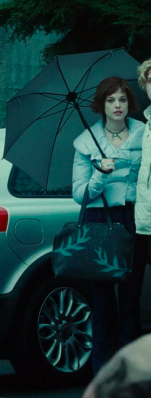 Alice wearing jeans, an ill-fitting winter jacket, a necklace, and a totebag