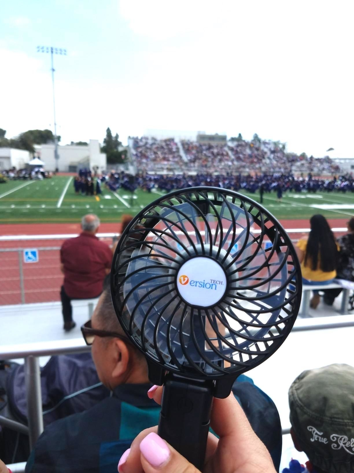 reviewer holding up a black personal fan outside