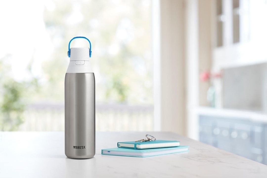 A stainless steel water bottle on a counter next to a two notebooks