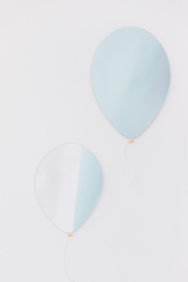two balloon mirrors hanging on the wall