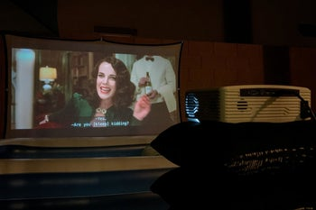reviewer watching a movie on the projector in their home