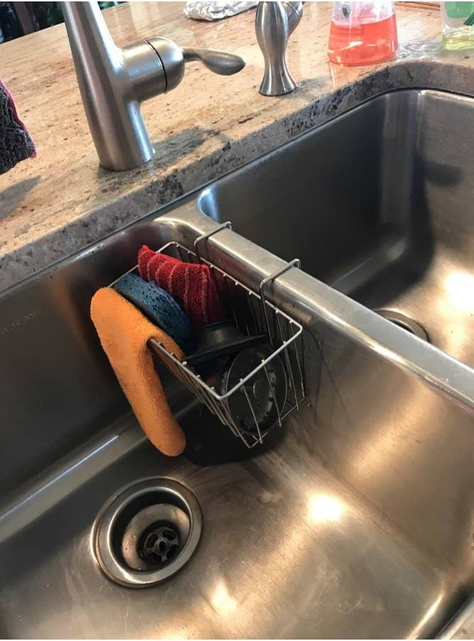 A stainless steel caddy in a sink, full of colorful sponges