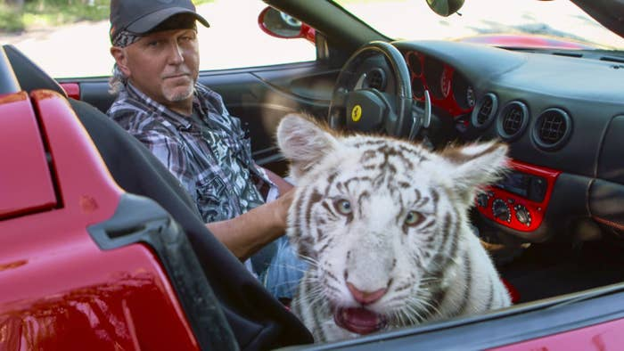 A man in the driver's seat of a sports car and a white tiger in the passenger seat look at the camera