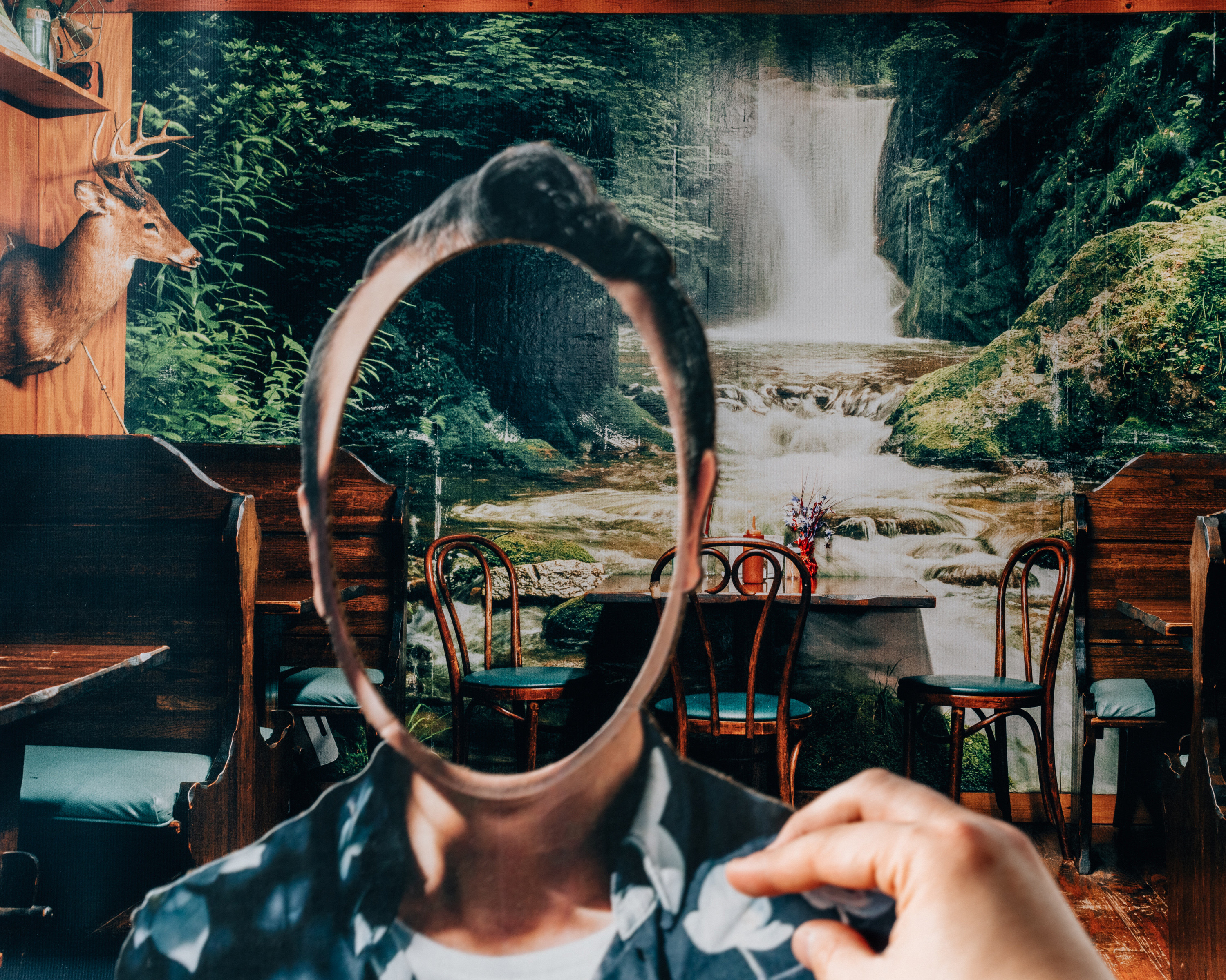 A photo collage shows someone's hand on a person's shoulder but with their face missing, revealing the background, a placid creek and waterfall scene, which appears to be wallpaper in a restaurant