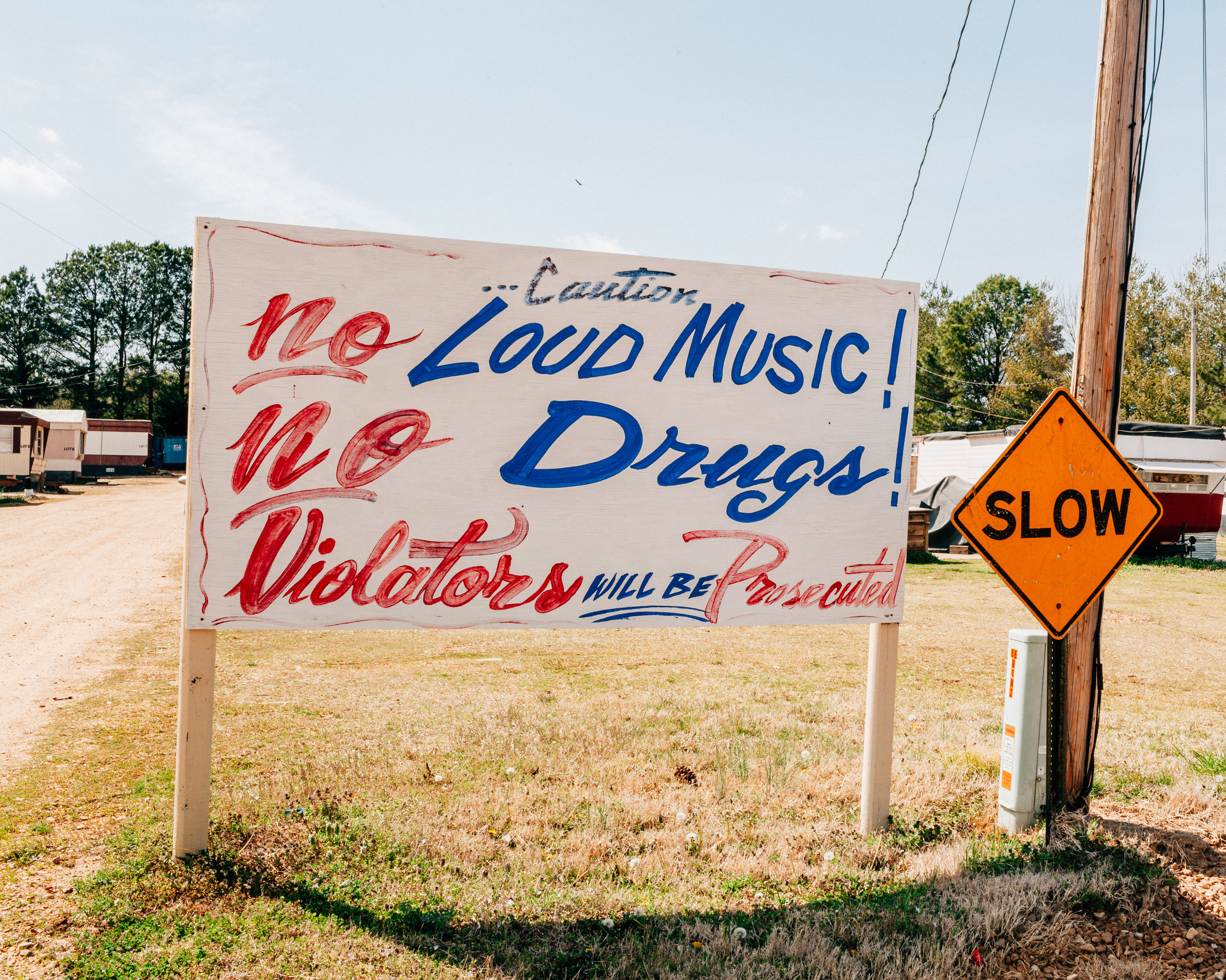 """A hand-painted sign reads """"no loud music, no drugs, violaters will be prosecuted"""""""