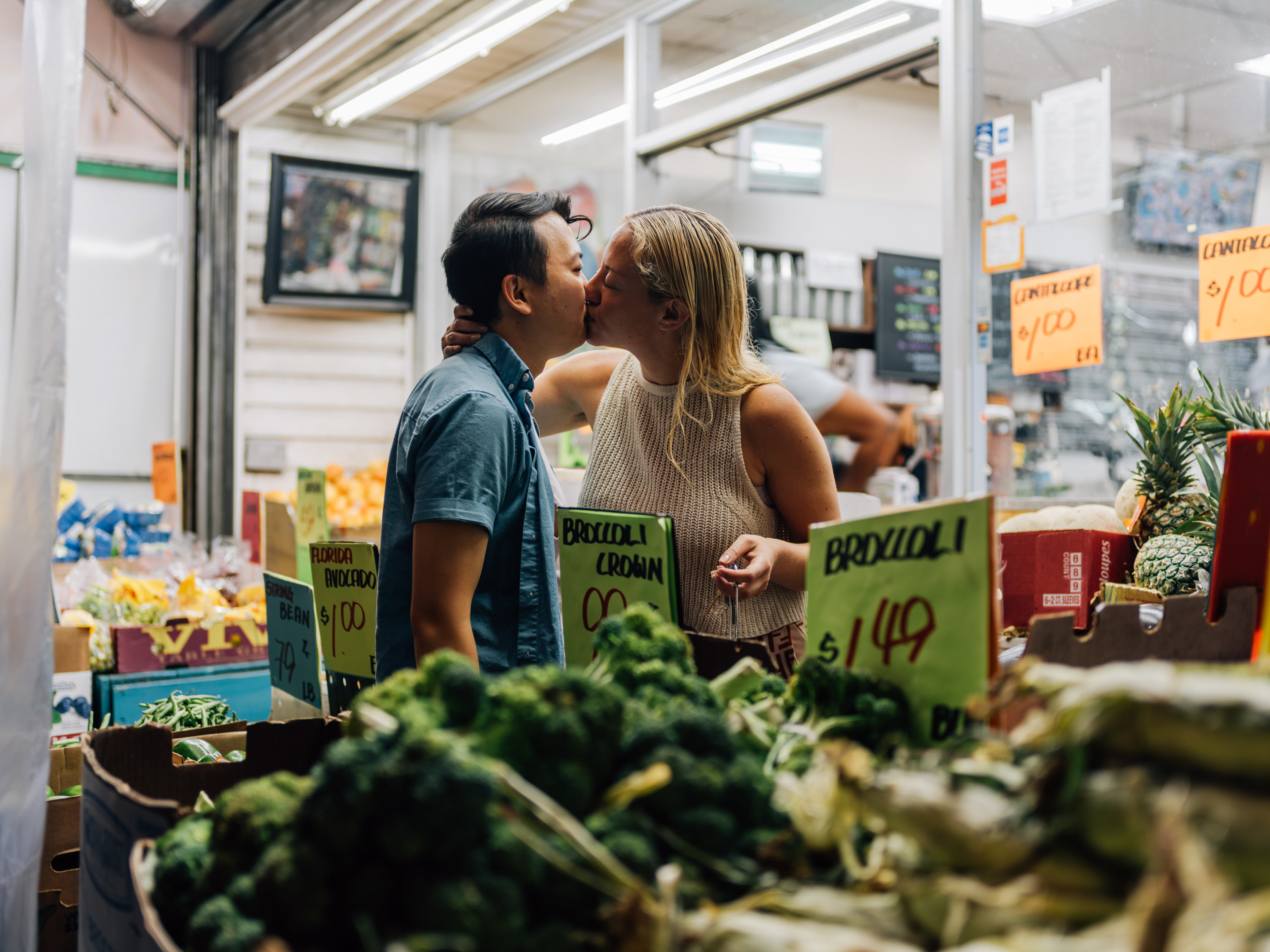 A woman leaning over and kissing the photographer outside a bodega